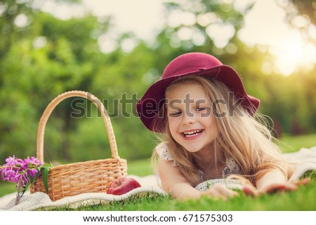 Little girl playing and eating in park on picnic