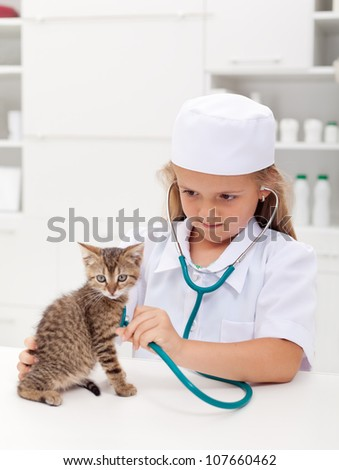 Little girl playing at the veterinary - consulting her little kitten