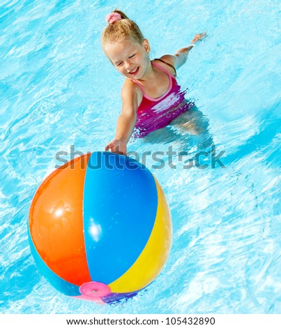 Little girl  playing beach ball in swimming pool.