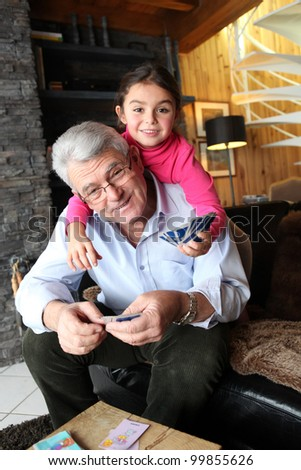 Little girl playing cards with grandpa