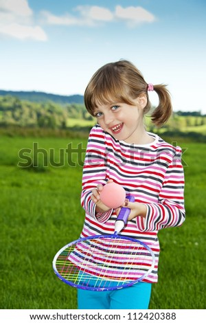 little girl playing children tennis on a meadow