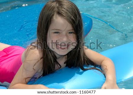 Little girl playing in backyard pool