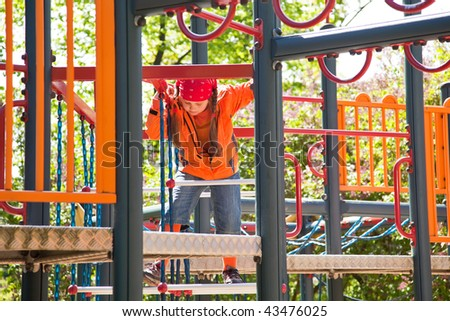 Little girl playing in jungle gym playground