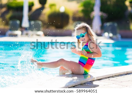 Little girl playing in outdoor swimming pool jumping into water on summer vacation on tropical beach island. Child learning to swim in outdoor pool of luxury resort. Water toy and sunglasses for kids. #589964051