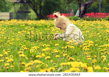 Little girl playing in the dandelion field. White dress with light brown bow. Red ribbon on her head. Red flowers background.