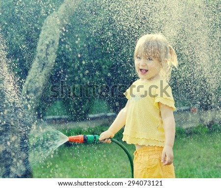 Little girl playing in the garden pouring all the water from a garden hose. MANY OTHER PHOTOS FROM THIS SERIES IN MY PORTFOLIO.