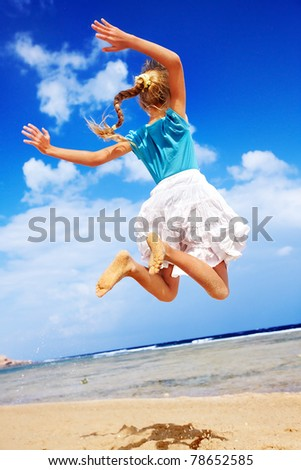 Little girl playing on beach against blue sky. lifestyle. - stock photo
