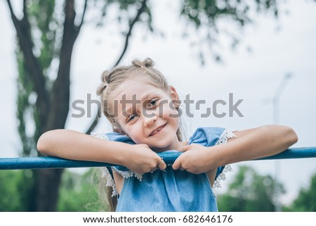 little girl playing on horizontal bar in park #682646176