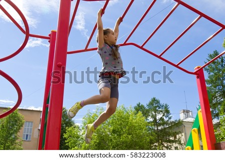 Little girl playing on playground, hanging walk along the monkey bars