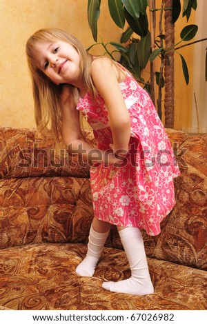 Little girl playing on sofa at her home and imagine she is model. Lifestyle.