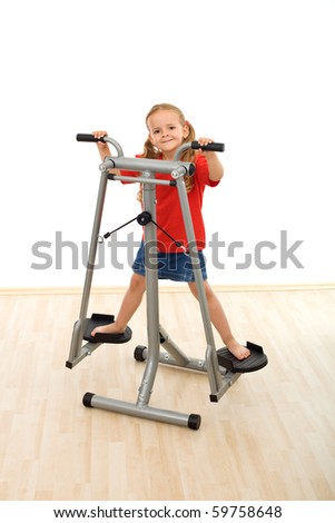 Little girl playing on stretcher device in the gym - isolated