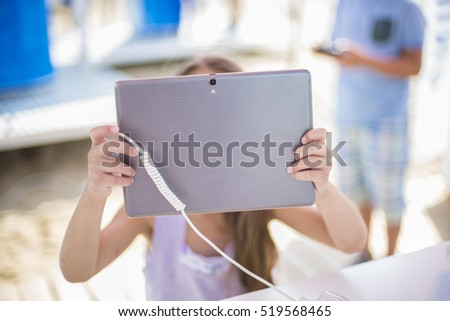 Little girl playing on tablet outdoor. Kid taking picture outside. Teenager with technology generation. Using tablet device.