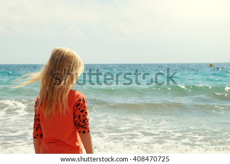 Little girl playing on the beach #408470725