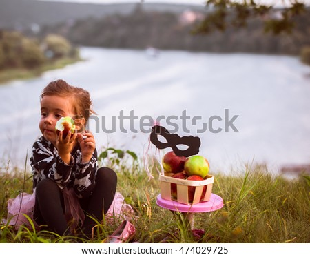 little girl playing on the grass in the daytime, the emotions of a child, a beautiful natural backdrop, playing with a mask #474029725