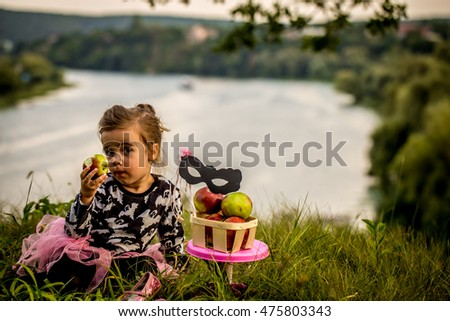 little girl playing on the grass in the daytime, the emotions of a child, a beautiful natural backdrop, playing with a mask #475803343