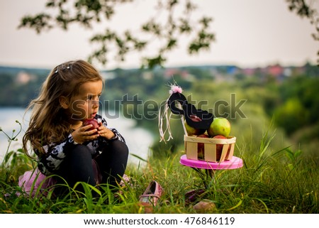 little girl playing on the grass in the daytime, the emotions of a child, a beautiful natural backdrop, playing with a mask #476846119