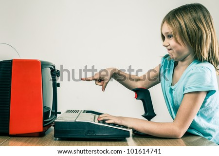 Little girl playing on vintage gaming equipment and pointing at television set