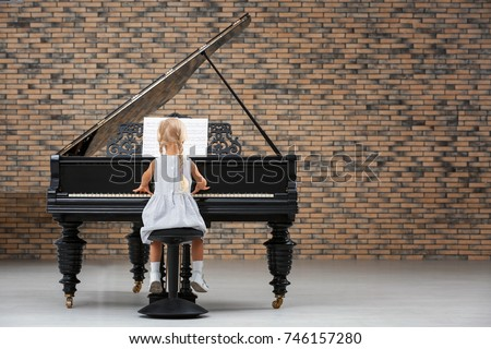 Little girl playing piano indoors #746157280