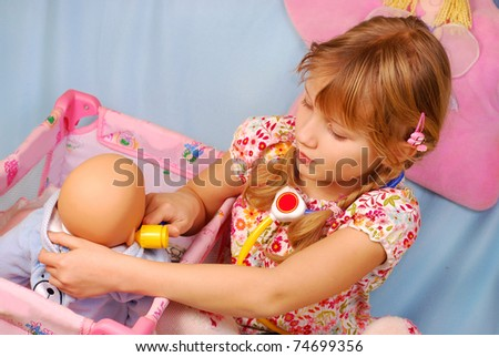 little girl playing the doctor with her newborn baby doll in room