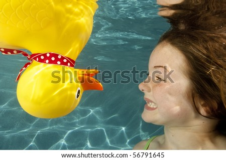 little girl playing underwater with large yellow rubber duck