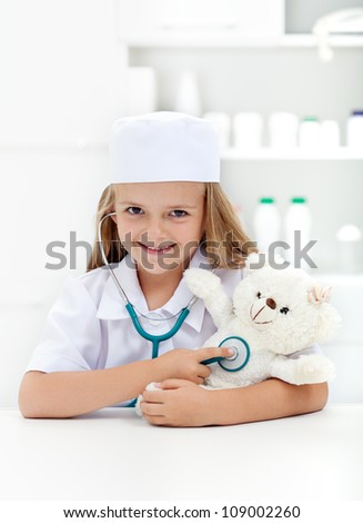 Little girl playing veterinary - examining her toy with stethoscope
