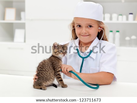 Little girl playing veterinary with her kitten - animal care concept