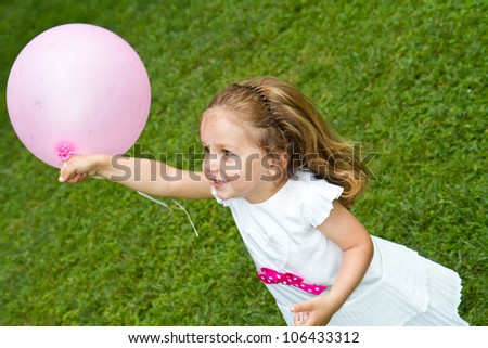 Little girl playing with balloon
