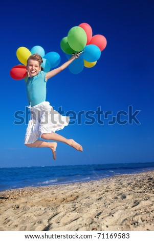 little girl playing with balloons at the beach. - stock photo