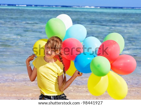 little girl playing with balloons at the beach.