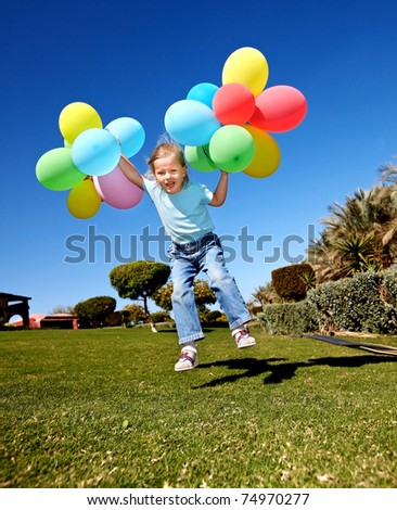 little girl playing with balloons in park.