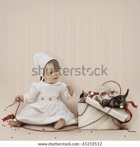 Little girl playing with beads and kittens in a gift box