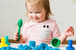 Little girl playing with blue kinetic sand. Educational games with children for fine motor skills. Sand therapy indoors. Concept of sensory and creativity game, therapy hand, development of fine motor