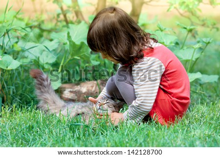 Little girl playing with cat on the grass