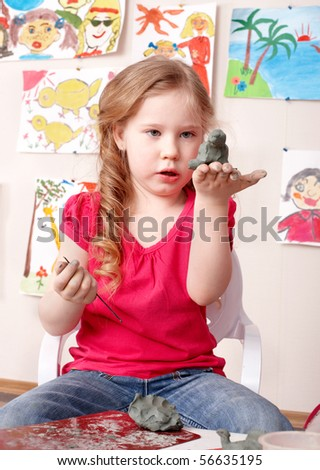 Little girl playing with clay.