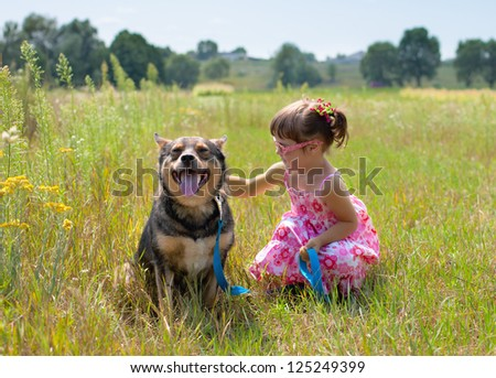 Little girl playing with dog at the meadow