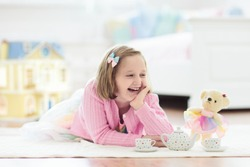Little girl playing with doll house in white sunny bedroom. Kid with toys. Role game for young children. Child with teddy bear toy. Kids play tea party with stuffed animals and dolls. Nursery interior