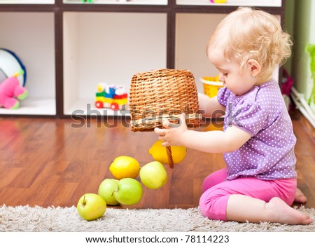 little girl playing with fresh fruit in her room