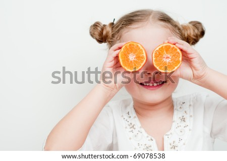 Little girl playing with fresh mandarin fruits - stock photo