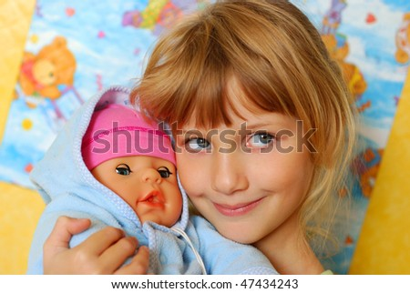 little girl playing with her baby doll and  pretending mom
