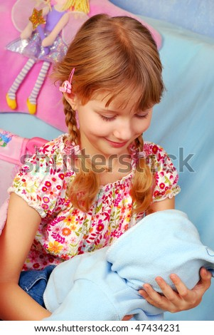 little girl playing with her baby doll pretending mom