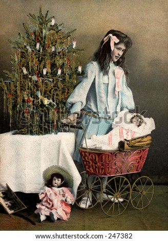 Little girl playing with her Christmas dolls and carriage - a 1907 vintage photo greeting card - stock photo