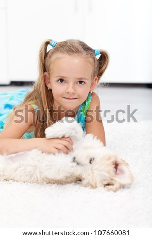 Little girl playing with her dog at home