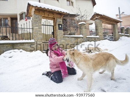 Little girl playing with her labrador friends