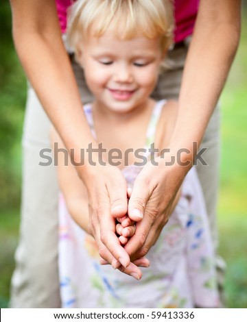 Little girl playing with her mom outdoors, shallow focus - stock photo