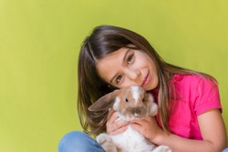 Little girl playing with her pet rabbit hugging her in a studio, with vivid colors