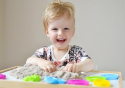 Little girl playing with kinetic sand at home, games, education, children
