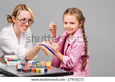 Little girl playing with mom, painting her fingers