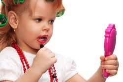 Little girl playing with mothers makeup and holding mirror