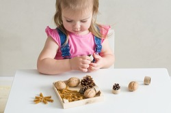Little girl playing with natural materials. Easy sensory activities for babies toddler, preschoolers. Activities Montessori, games for sensory processing disorder, child development