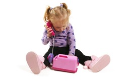 Little girl playing with pink toy phone